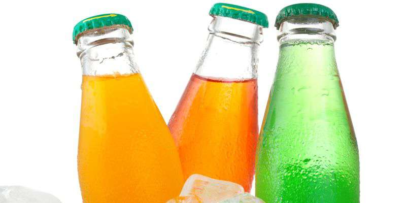 Bottles with soda in ice on white background