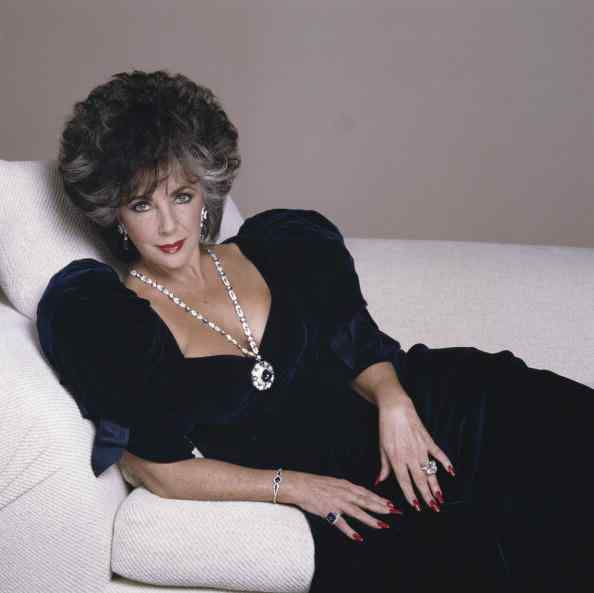English born actress Elizabeth Taylor posing in a midnight blue velvet evening gown with sapphire and diamond jewllery, Beverly Hills 1988. (Photo by Terry O'Neill/Getty Images)